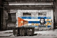 Svartvit bild av gamla sjaskiga byggnader i havannacigarr med en målning av Che Guevara och en kubansk flagga Royaltyfri Fotografi