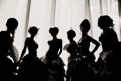 Svartvit bild av konturn av flickor och kvinnor i karnevaldräkter och bollklänningar i teatern på etappbehinen royaltyfria foton