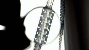 Svartvit film 16mm beskådas till och med lumenen Första-personen beskådar arkivfilmer