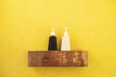 Svartvit flaskbehållare på trähylla i toalett med den gula väggen royaltyfri foto