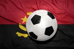 Svartvit fotbollboll på nationsflaggan av Angola Arkivfoton