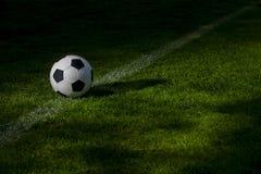 Svartvit fotbollboll p? den gr?na fotbollgraden royaltyfri foto