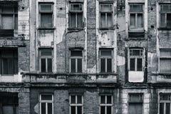 Svartvit halva-förstörd framdel av det grungy byggandet och hög-kontrast arkivbild