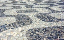 Svartvit iconic mosaik, portugisisk trottoar vid den gamla designmodellen på den Ipanema stranden, Rio de Janeiro royaltyfri bild