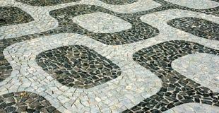 Svartvit iconic mosaik, portugisisk trottoar vid den gamla designmodellen på den Ipanema stranden, Rio de Janeiro royaltyfri foto