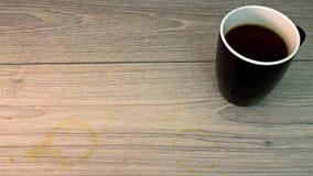 Svartvit kaffekopp med kaffefläck på golv Royaltyfri Bild