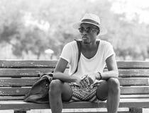 Svartvit livsstilmodestående Stilfull ung afrikansk man som bara sitter på solglasögon och gnäggandet för en parkerabänk bärande arkivbilder