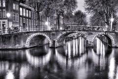 Svartvit nattsikt av Amterdam Cityscape med en av dess kanaler Med den upplysta bron och traditionella holländska hus royaltyfria bilder