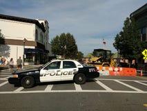 Svartvit polisbil som blockerar vägen Royaltyfri Foto