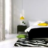 Svartvit säng och en gul lampa Royaltyfri Fotografi
