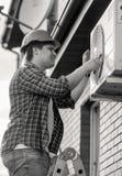 Svartvit stående av att le teknikeren som reparerar det betingande systemet för luft Arkivfoton