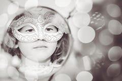 Svartvit stående av en härlig flicka i karnevalmaskeringslo Arkivfoto