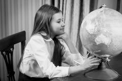 Svartvit stående av skolflickan som ser det stora jordklotet på t Royaltyfri Foto