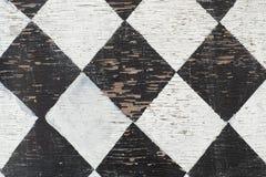 Svartvit tegelplattamodell som målas på wood textur arkivfoton