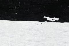 Svartvit vägg i form av en flagga Väggnärbild med skalning av murbruk och av suddig vit och svart målarfärg royaltyfri bild