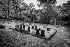 Svartvita allvarliga markörer på en gammal kyrkogård arkivbilder