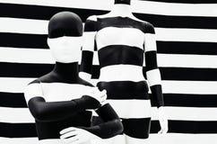 Svartvita band för konstskyltdocka, på randigt med svartvita band förklädnad Arkivbild