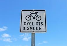 Svartvita cyklister stiger av undertecknar in en blå himmel Arkivbilder