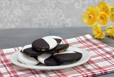 Svartvita kakor på ett ovalt uppläggningsfat som staplas royaltyfri bild