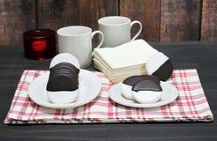 Svartvita kakor upprätt på en platta Tabellinställningen inkluderar kakor på en platta royaltyfria foton
