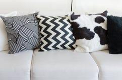 Svartvita kuddar på den vita soffan i vardagsrum hemma Royaltyfri Fotografi
