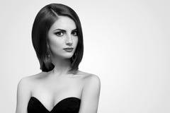 Svartvita studioskott av en flott ung kvinna med kortslutning royaltyfri foto