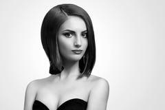 Svartvita studioskott av en flott ung kvinna med kortslutning royaltyfria foton