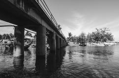 Svartvitt bildbegrepp av den konkreta bron som korsar floden med bakgrundsgruppen av fartyg Royaltyfri Foto