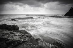 Svartvitt bildvågflöde på den sandiga och steniga stranden Arkivfoton