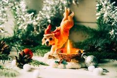 Svartvitt chihuahuasammanträde på en filt som omges av leksaker och julpynt, ser ledset åt sidan År av hunden 2018 royaltyfria bilder