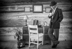 Svartvitt foto av den caucasian mannen i en dräkt som rymmer en kaffekopp royaltyfria foton