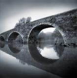 Svartvitt foto av den forntida romanska bron Royaltyfri Foto