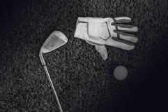 Svartvitt foto av golfklubbar och en golfboll i lågt ljus royaltyfria foton