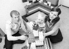Svartvitt foto av lyckliga föräldrar som spelar tegelstenar Royaltyfri Bild