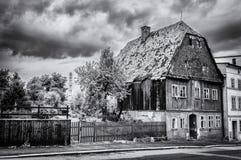 Svartvitt fotografi av ett stort hus med en trädgård vid dess sida och trottoar framme Royaltyfria Bilder