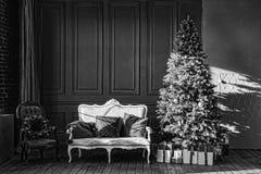 Svartvitt julgran i kunglig inre Nytt års vardagsrum med den antika stilfulla vita soffan med lyxigt guld- royaltyfri bild