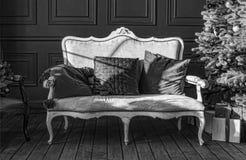 Svartvitt julgran i kunglig inre Nytt års vardagsrum med den antika stilfulla vita soffan med lyxigt guld- royaltyfri foto