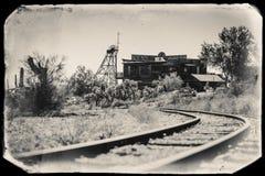 Svartvitt Sepiatappningfoto av gamla drevspår i spökstad för guld- min för guldfält i Youngsberg, Arizona fotografering för bildbyråer
