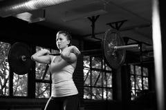 Svartvitt skott av kvinnan i idrottshalllyftande vikter Arkivfoto