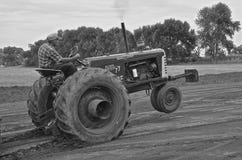 Svartvitt: Traktor som drar strid Fotografering för Bildbyråer