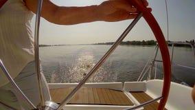 Svegli dalla barca a vela sull'acqua, barca della direzione della donna al tramonto archivi video