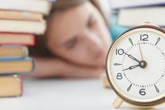 Sveglia accanto alla ragazza che dorme fra le pile di libri Concetto di formazione immagini stock libere da diritti