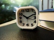 Sveglia bianca accanto alla pila di libro sulla tavola fotografia stock libera da diritti
