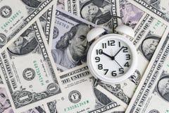 Sveglia bianca sulle banconote del dollaro americano come tempo per soldi informati Fotografie Stock