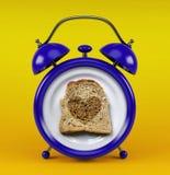 Sveglia blu con il concetto del cuore del pane del pane tostato isolata su fondo giallo Fotografia Stock Libera da Diritti