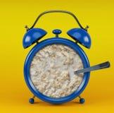 Sveglia blu con il concetto del porridge su fondo giallo Fotografia Stock Libera da Diritti