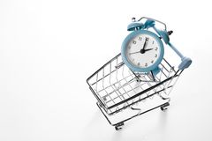 Sveglia blu nel carrello di compera su un fondo bianco Concetto - tempo di comprare Vista da sopra immagini stock libere da diritti