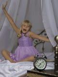 Sveglia che sta sul comodino Svegli di una ragazza addormentata sta allungando a letto nel fondo Immagine Stock