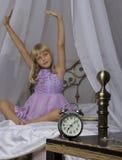Sveglia che sta sul comodino Svegli di una ragazza addormentata sta allungando a letto nel fondo Immagini Stock