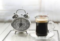 Sveglia con la tazza di caffè ed il fondo bianco FO selettive immagine stock